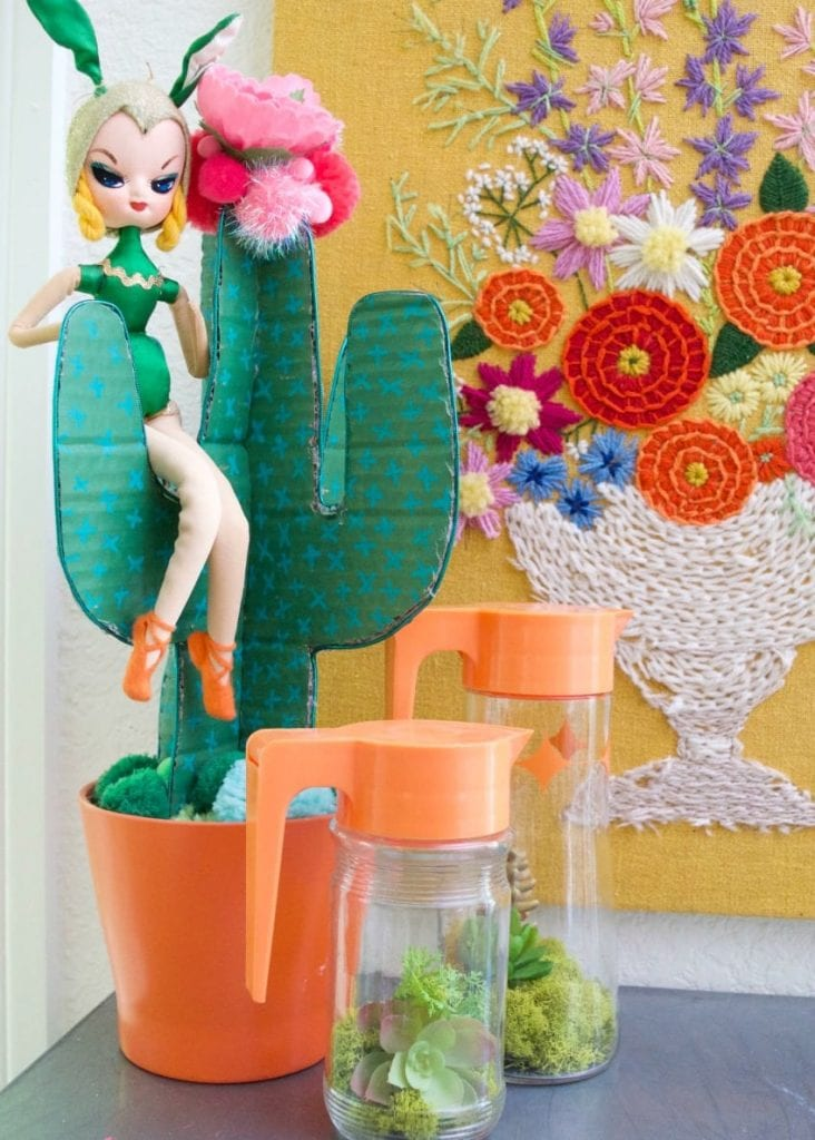 Terrariums made of vintage pitchers and syrup jars with Pose doll and cardboard cactus.