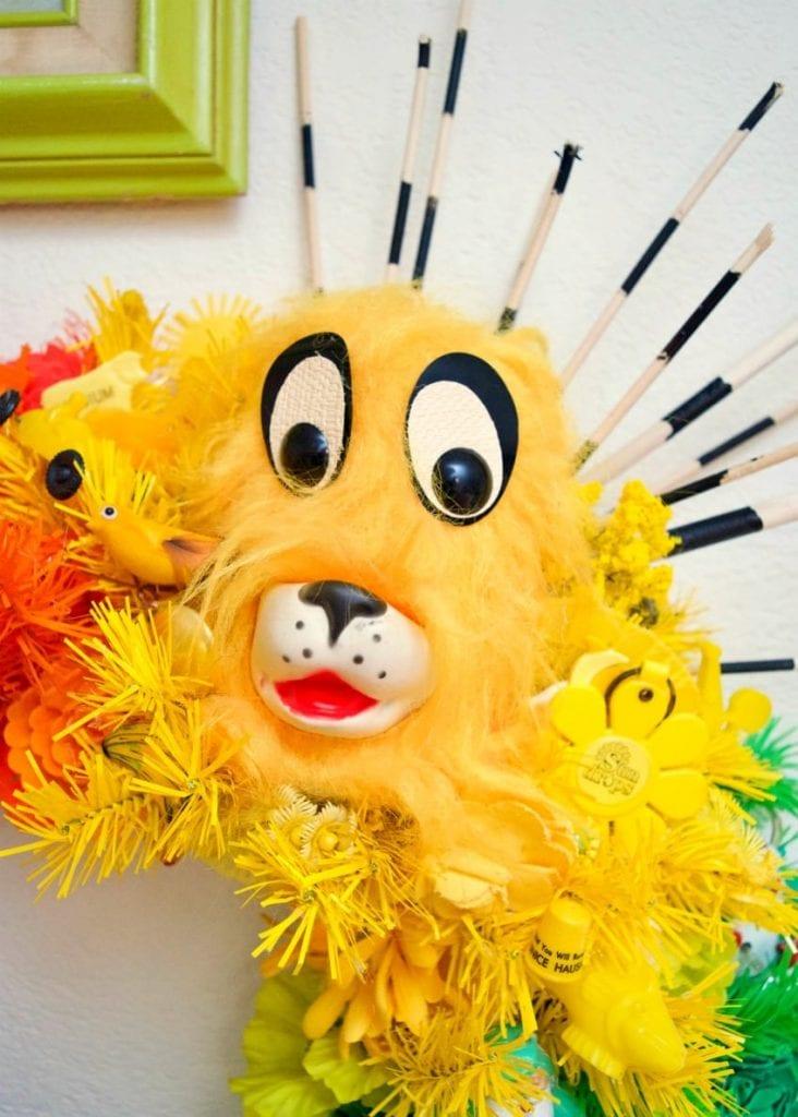 Kitschy yellow vintage doll on a rainbow wreath.