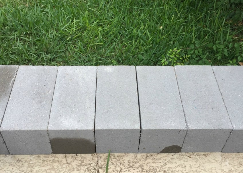 cinderblocks lined up on a patio to form the base of a bench.