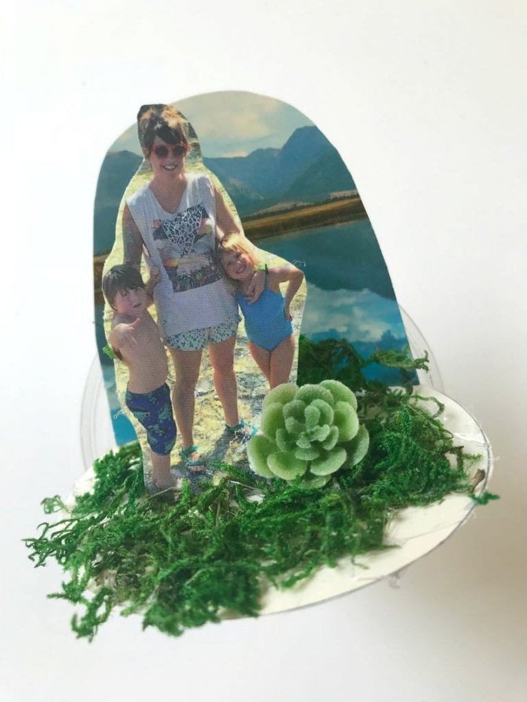 Cut photographs and postcards cut down to go inside DIY cup snow globes.