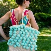 Straw beach bag with pompom yarn woven in.
