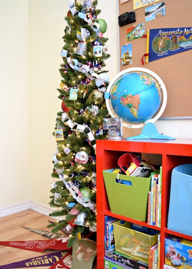 Green Christmas tree with a travel theme and a globe.