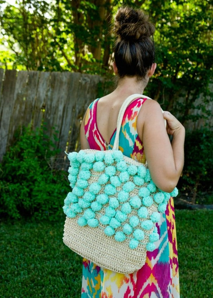 Beach bag with aqua pompoms.