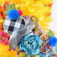 Close up of a yellow tree with faux flowers and checkered deco mesh