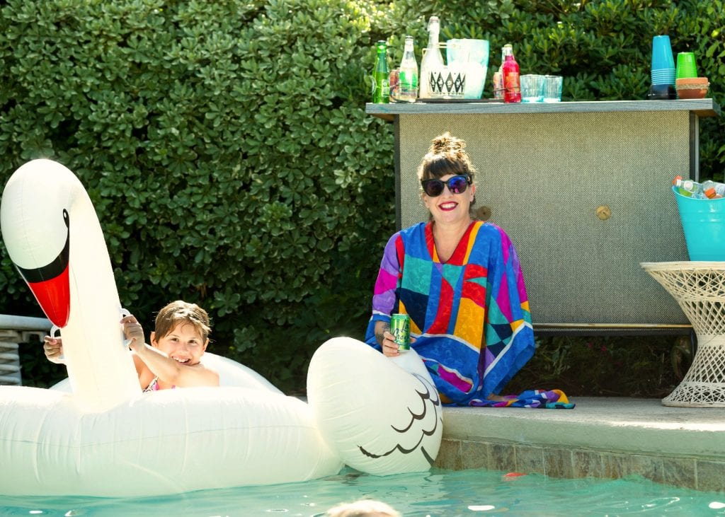 Pool party with family. Mom in caftan kid on swan float.