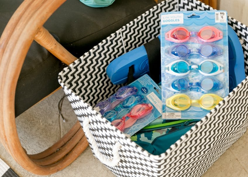 Outdoor basket full of googles and swim floats.