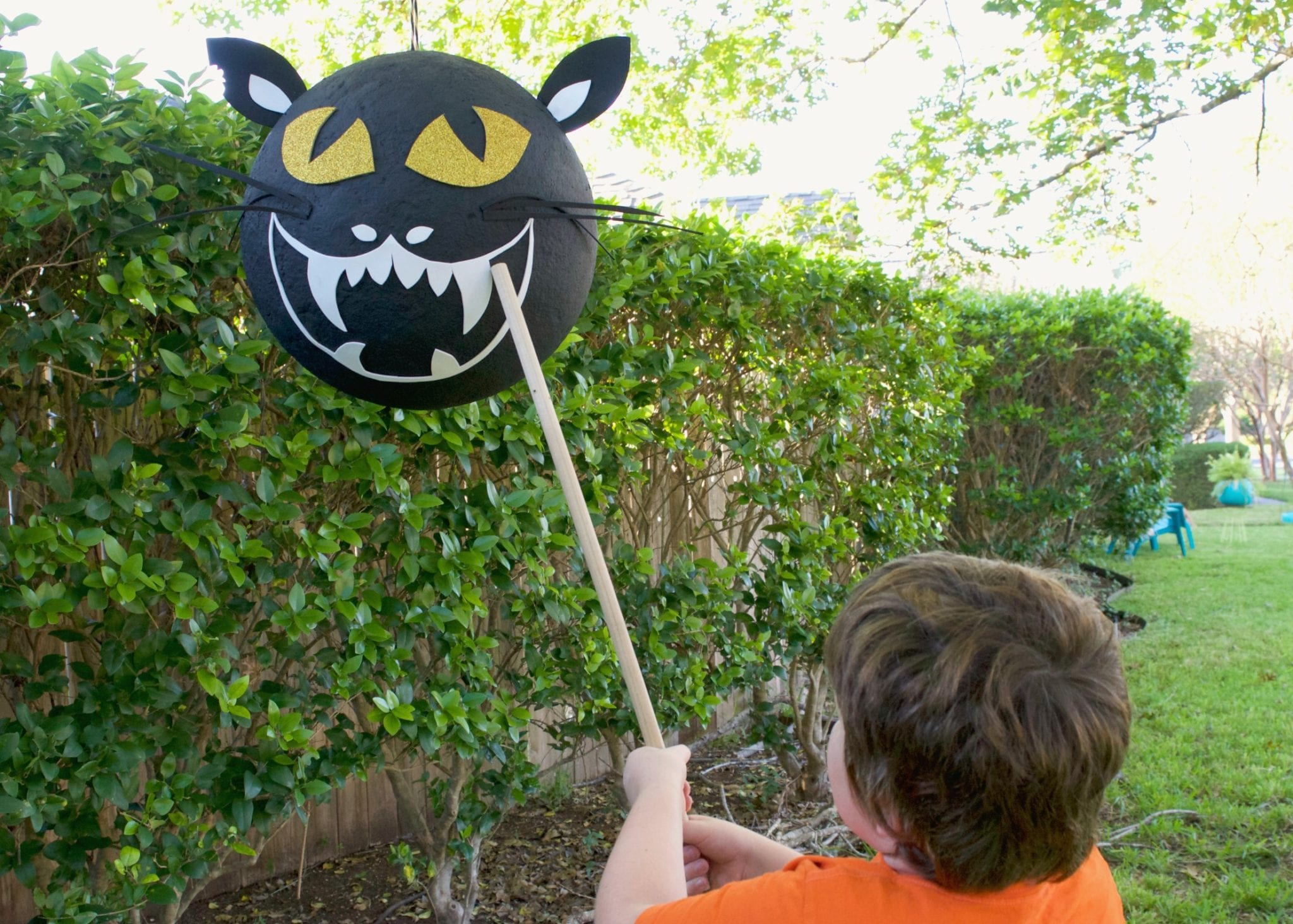 Child hitting a paper-mache Halloween piñata that looks like a black cat.
