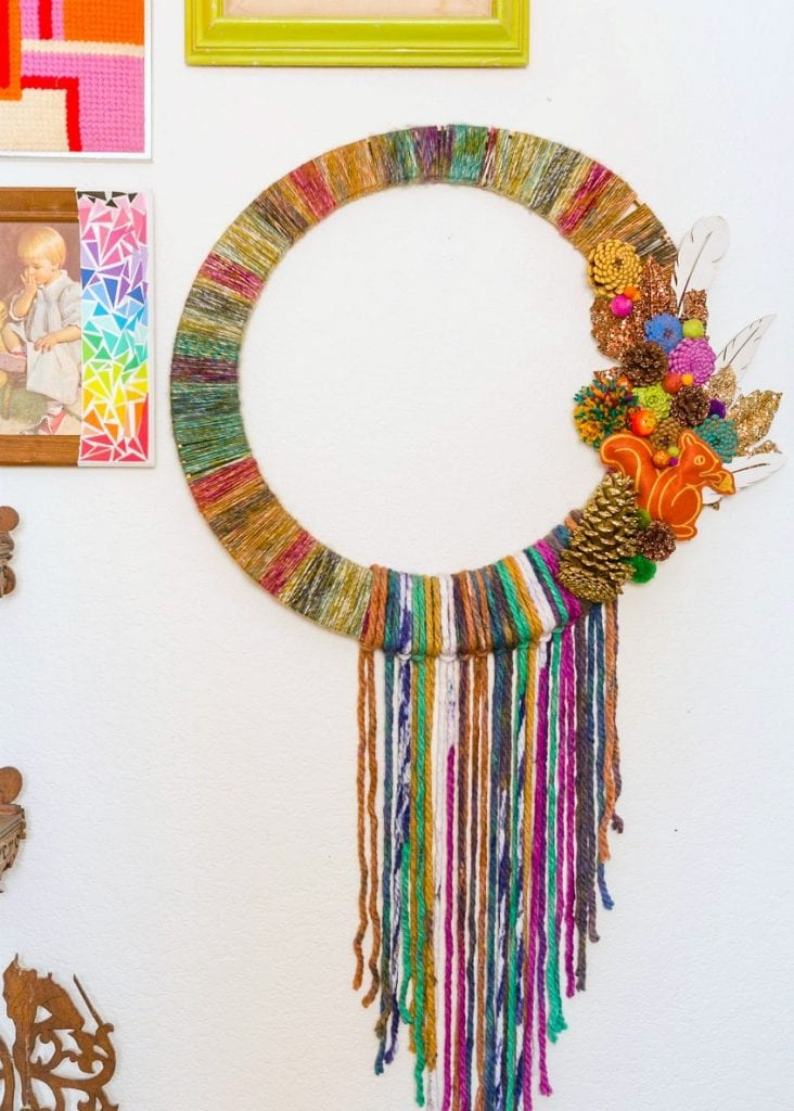 Fall wreath wrapped in yarn with pinecones hanging on a wall
