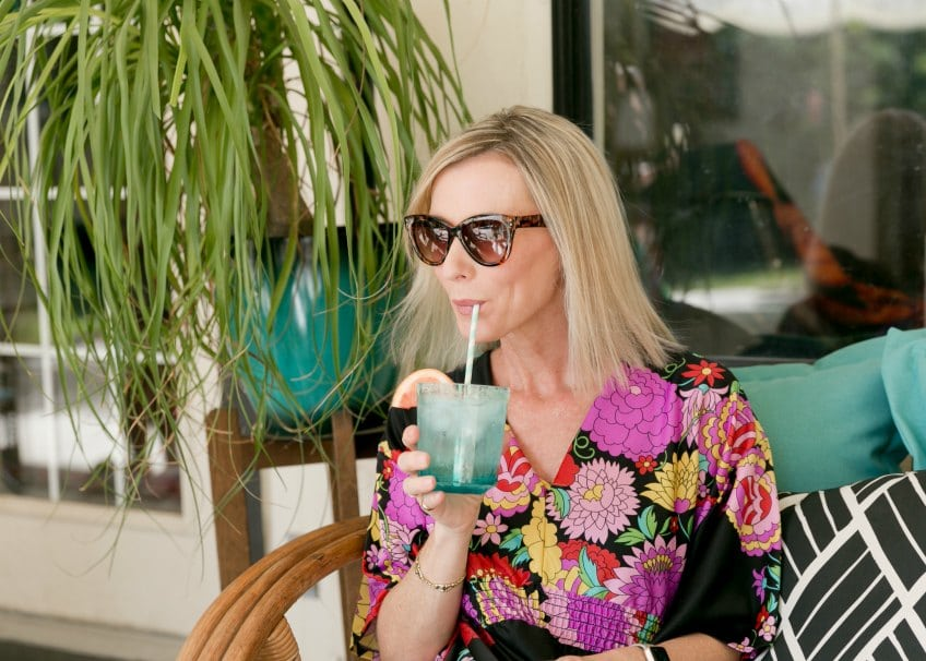 Woman drinking a mocktail on a patio wearing a caftan.