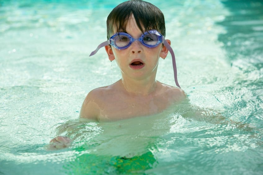 Kid in a pool with goggles on