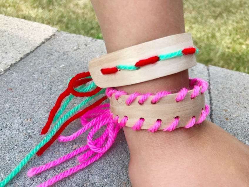 Kid wearing a craft bracelet laced with pink yarn