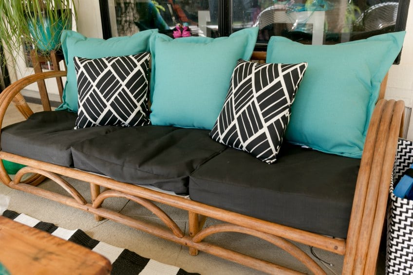 Outdoor sofa with teal and black throw pillows on a patio.