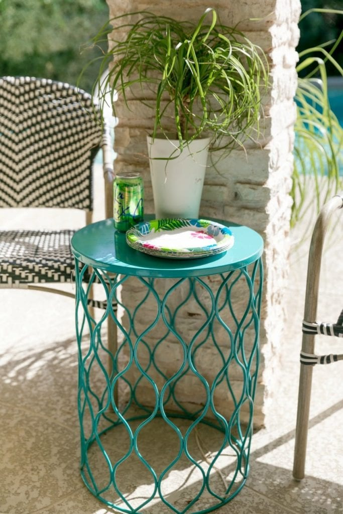 Teal outdoor table with plant and plates.