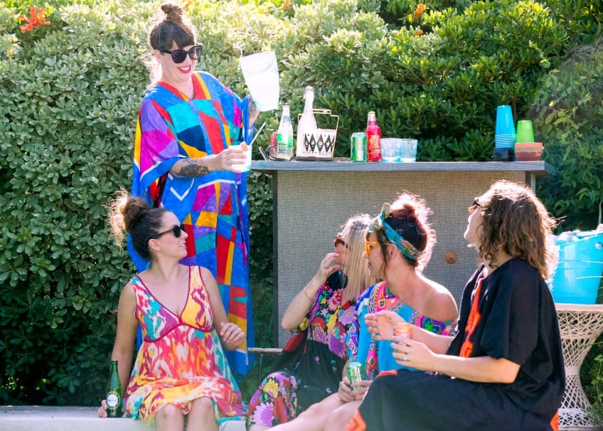 Ladies outside at a mocktail water bar beside the pool.