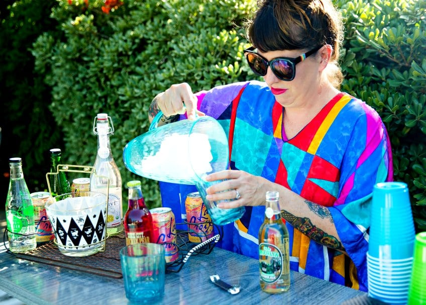 Jennifer Perkins pouring mocktails at an outdoor pool party with a water bar.