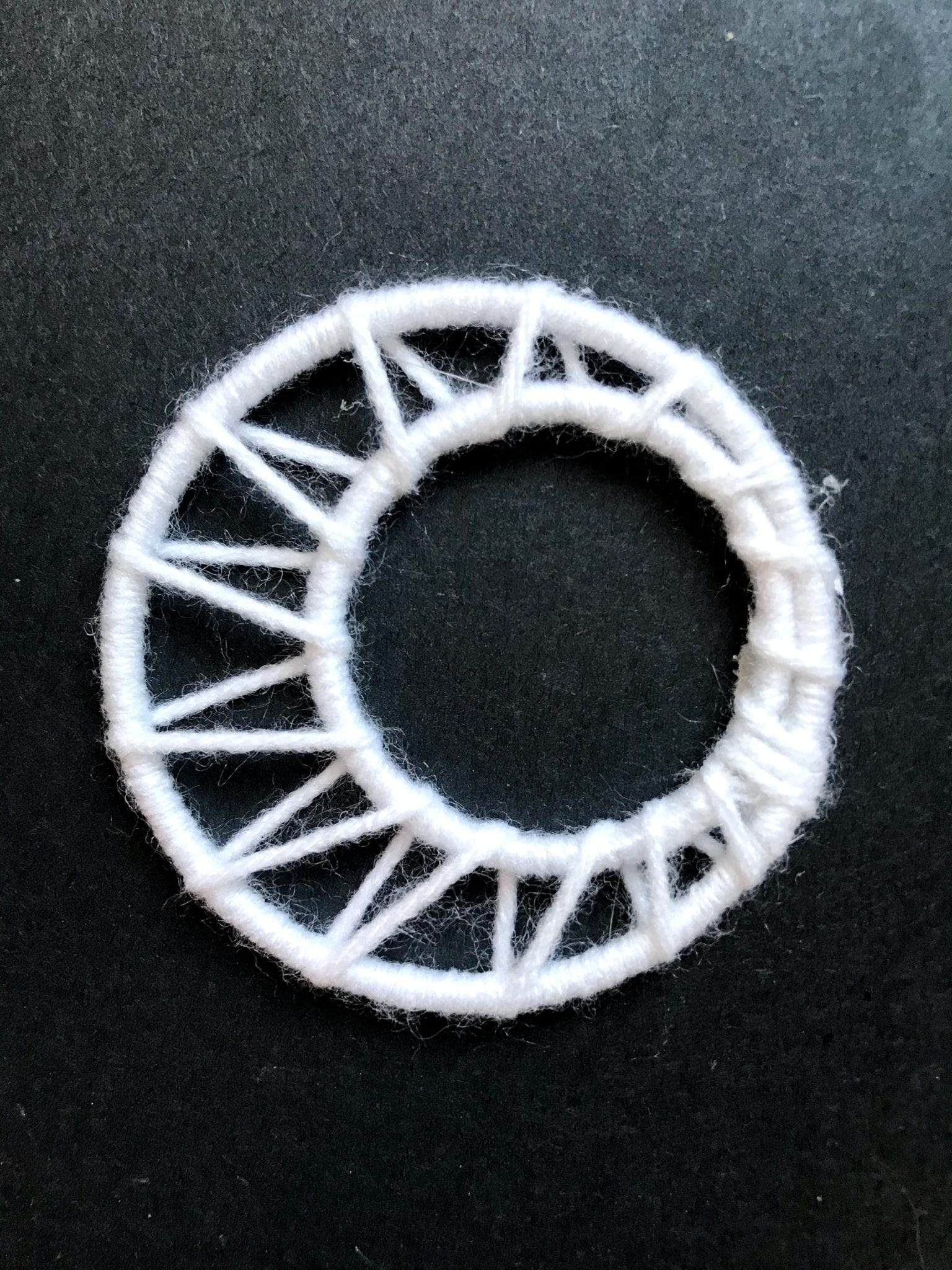 Two yarn wrapped rings that look like a moon