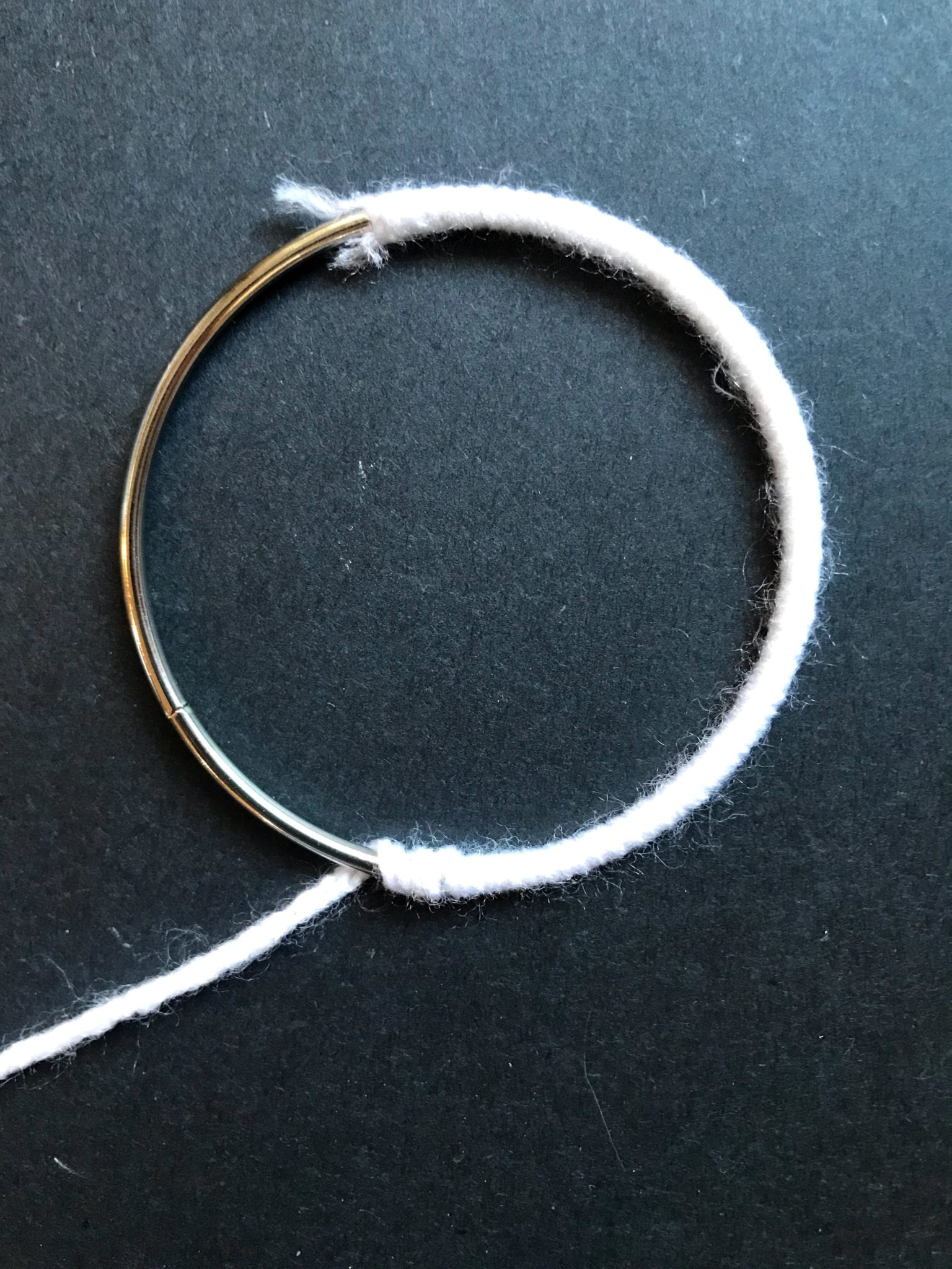 Metal ring being wrapped with white yarn