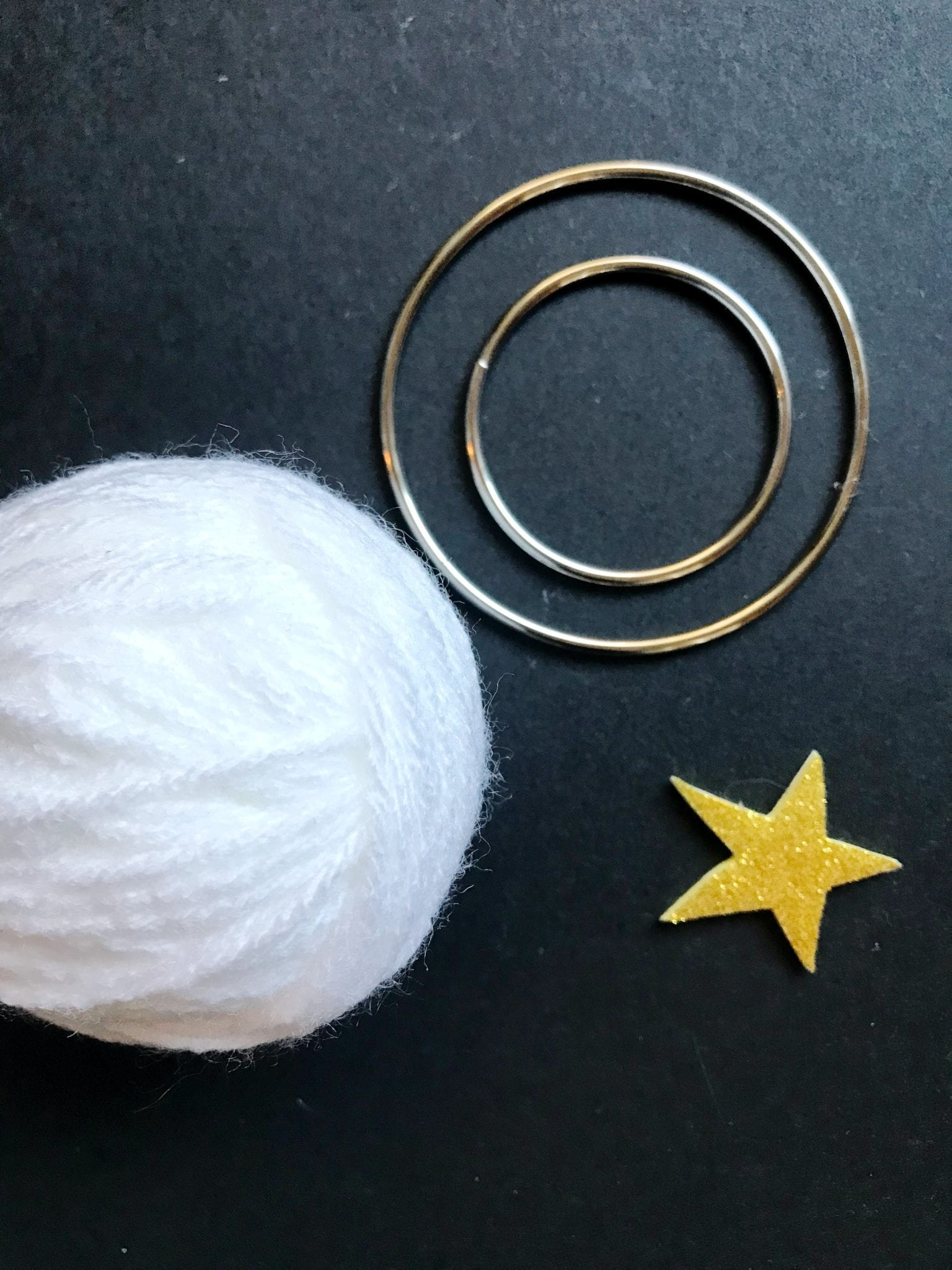Supplies for a DIY moon ornament including yarn, star stickers and metal rings.