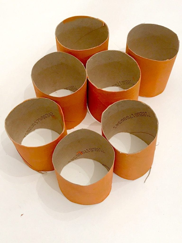Toilet paper tubes painted orange and cut in half