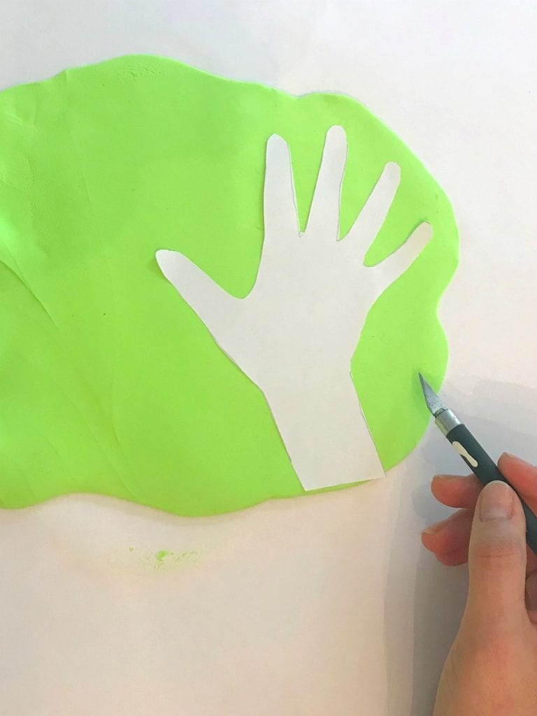 Traced clay hand being cut out with craft knife