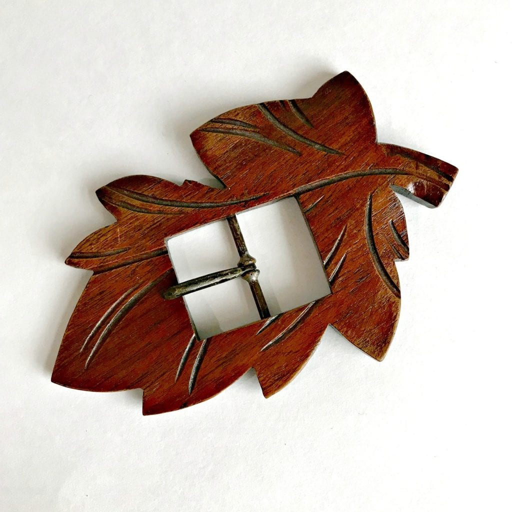 Large vintage wooden belt buckle shaped like a leaf.