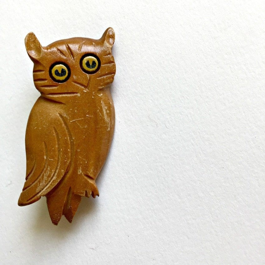 wooden owl pin with yellow eyes