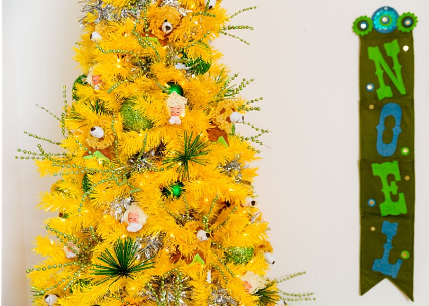 Yellow Christmas tree with green decorations and vintage felt noel sign.
