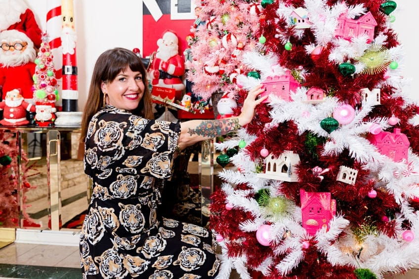 Jennifer Perkins decorating a candy cane colored Christmas tree.