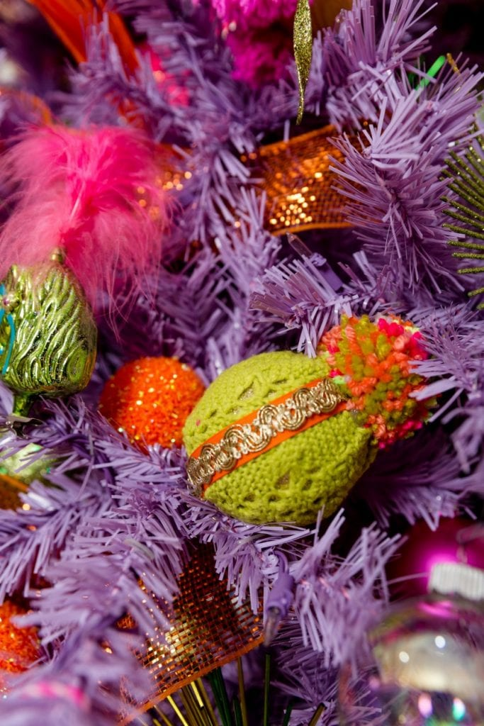 green christmas ornament on a purple tree