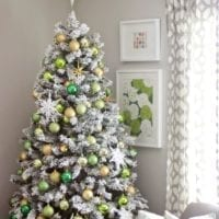 Flocked Christmas tree with green and gold ornaments
