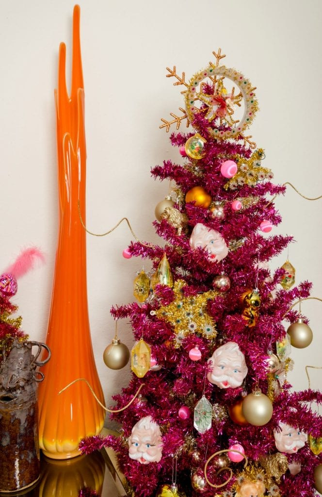 Magenta Christmas tree covered with vintage tree toppers