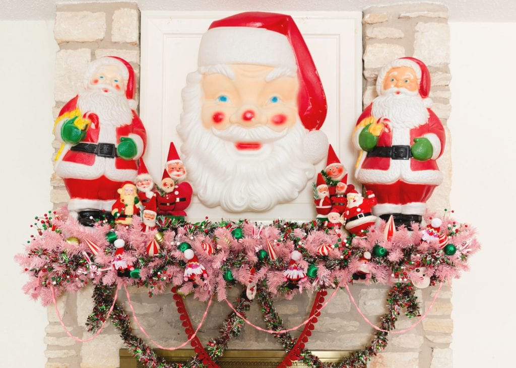 Large Santa Claus blow molds with a pink garland