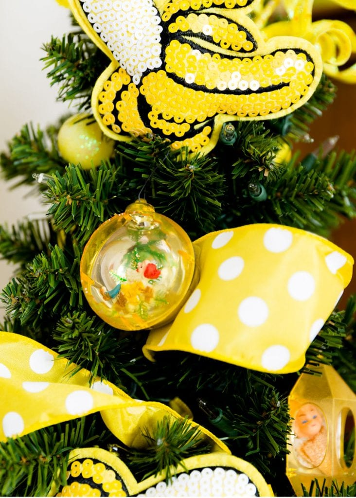 Yellow Jewel Brite ornament on a green tree with yellow ribbon