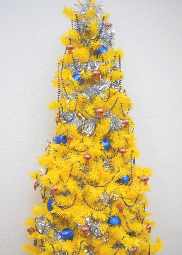 Yellow artificial Christmas tree with navy blue decorations and football whistles