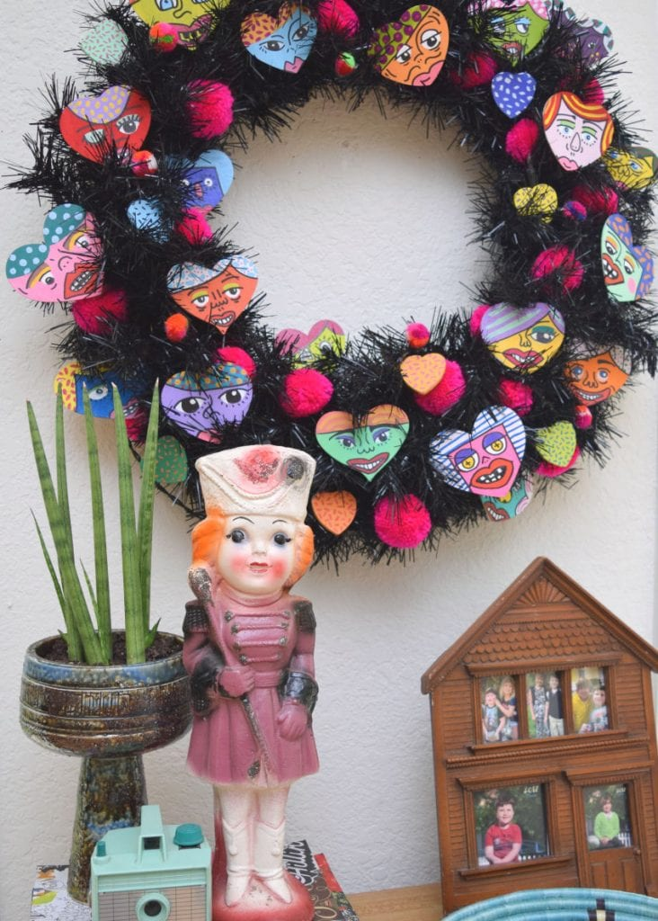 Black wreath covered in hand painted hearts for Valentine's Day