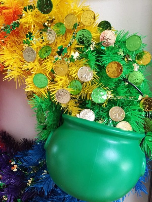 Green pot on a rainbow wreath with lucky coins