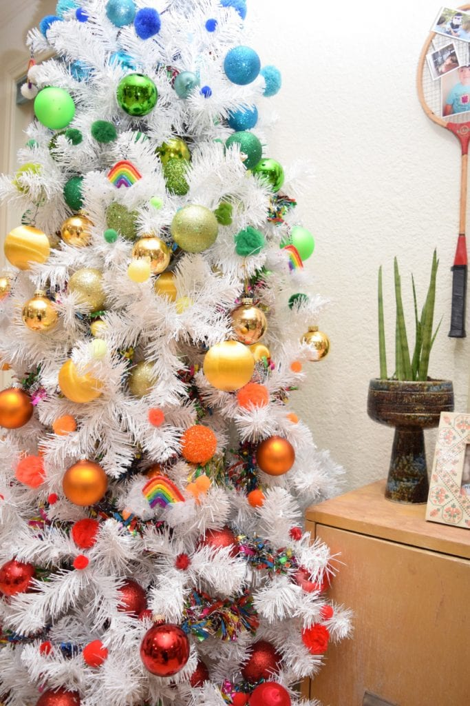 white Christmas tree decorated with rainbow ornaments