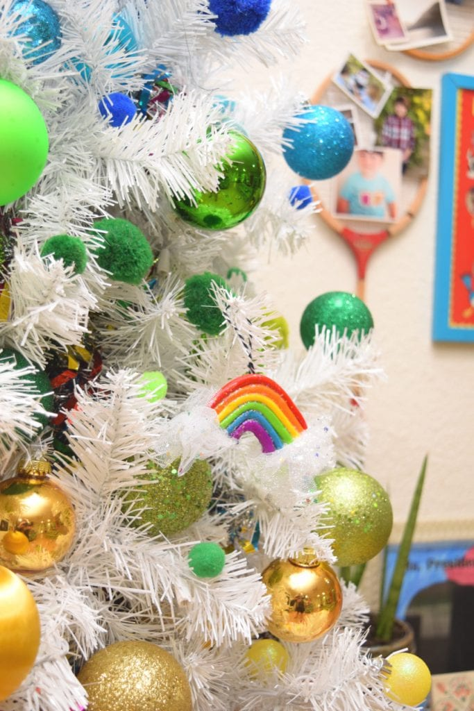 DIY rainbow Christmas ornament on white tree.