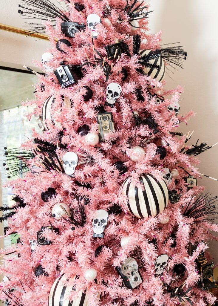 Pink Christmas tree decorated for Halloween with black and white skeletons and pumpkins