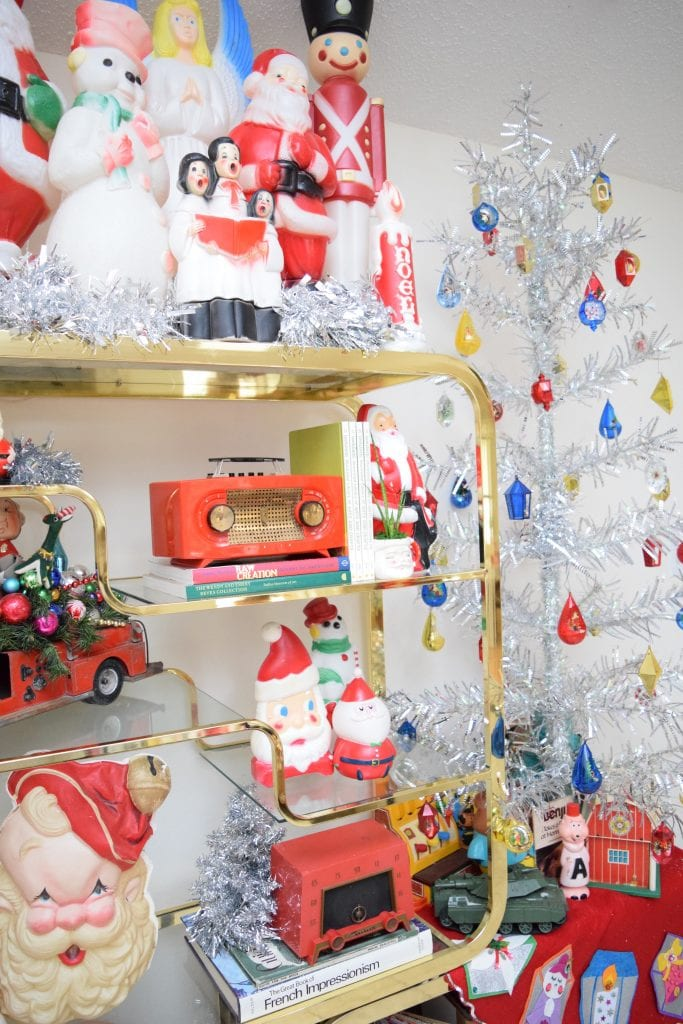 Vintage Christmas blow molds and a silver tinsel tree on a brass etagere.