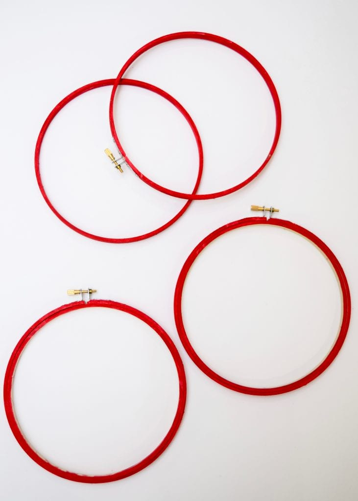 wooden embroidery hoops painted red for a hanging wall pocket craft project.
