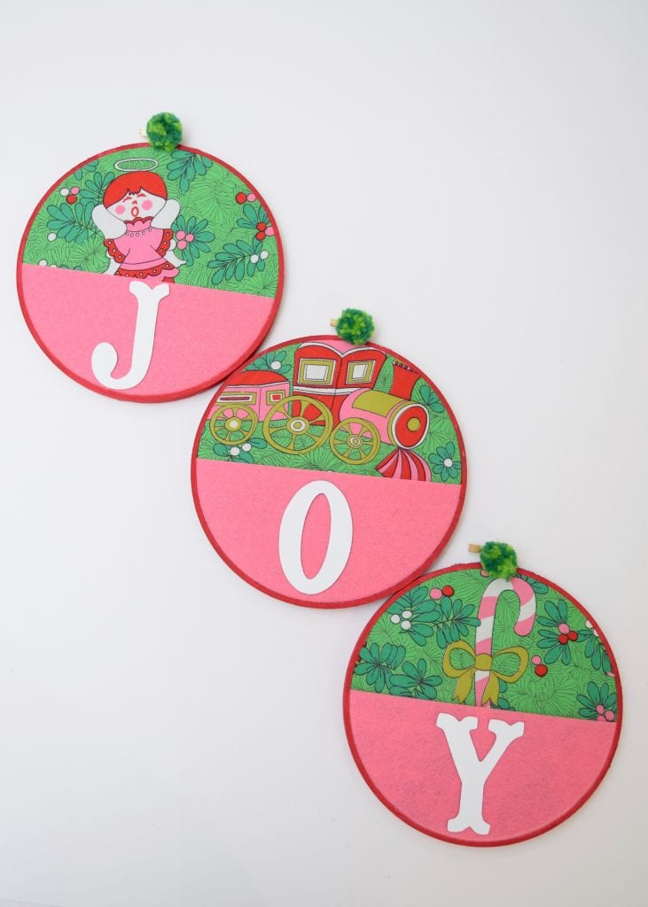 DIY wall pockets for Christmas cards that say JOY made from embroidery hoops.