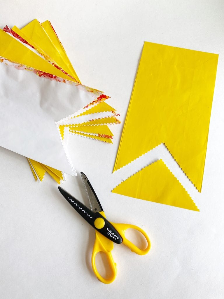 Yellow gift bag being trimmed to form a hanging party star.