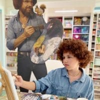 Kid painting dressed as Bob Ross