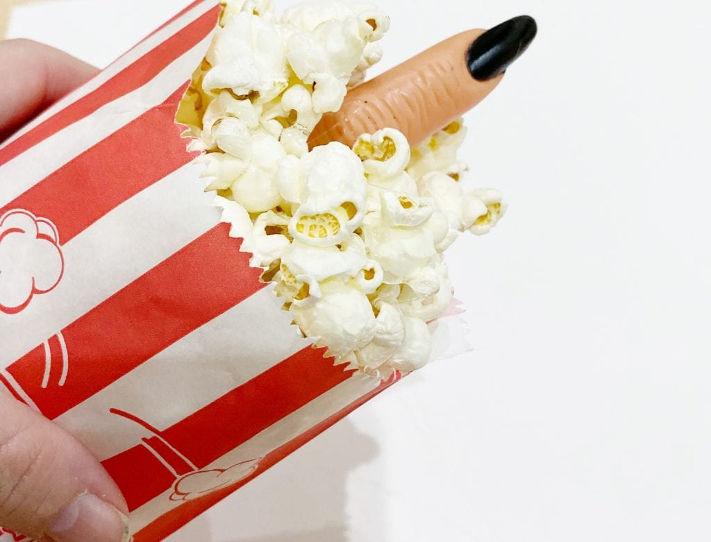 Striped popcorn bag with finger sticking out for Halloween