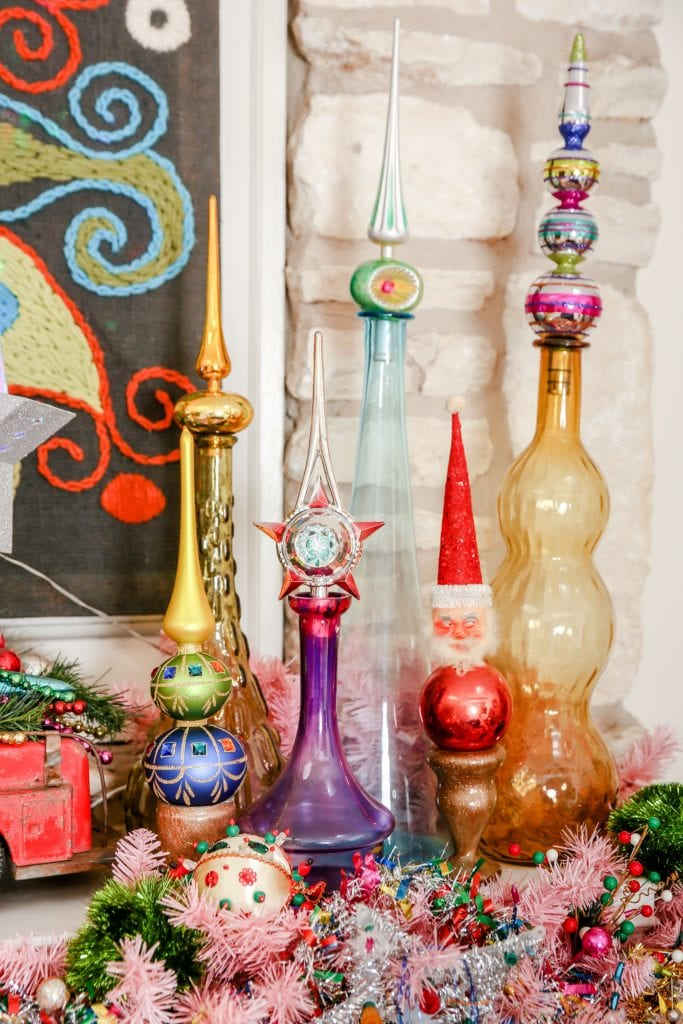 Colorful vintage glass bottles displaying Christmas tree toppers.