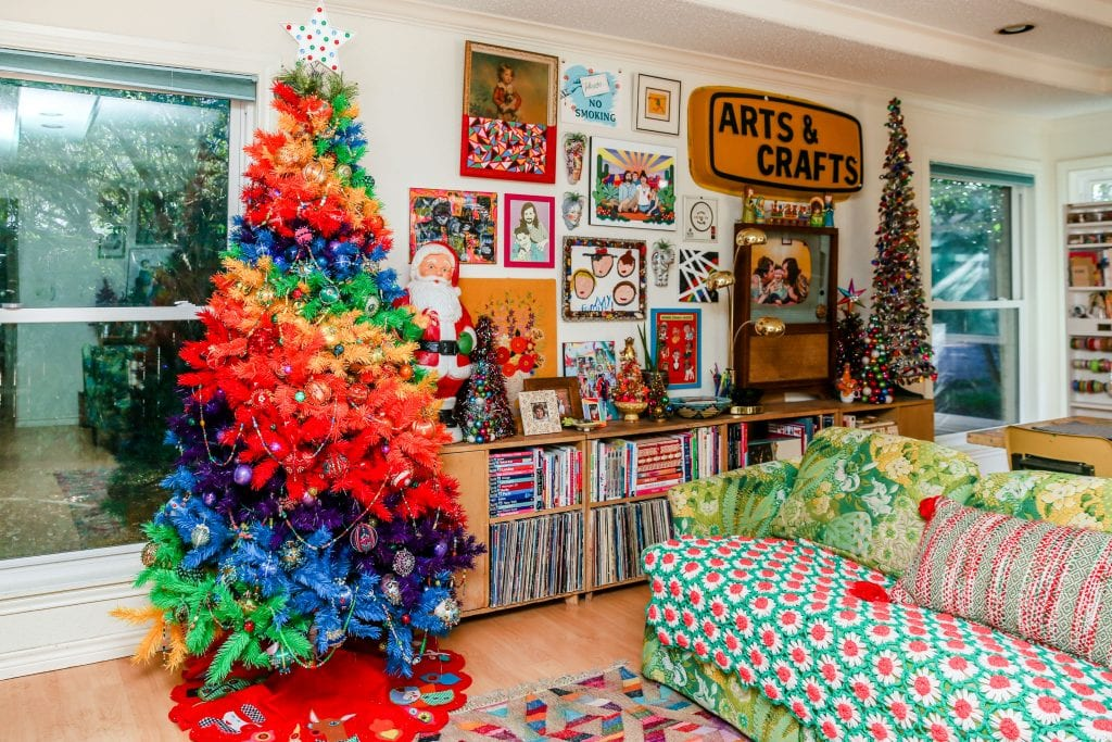 Rainbow striped Christmas tree in an eclectic living room.