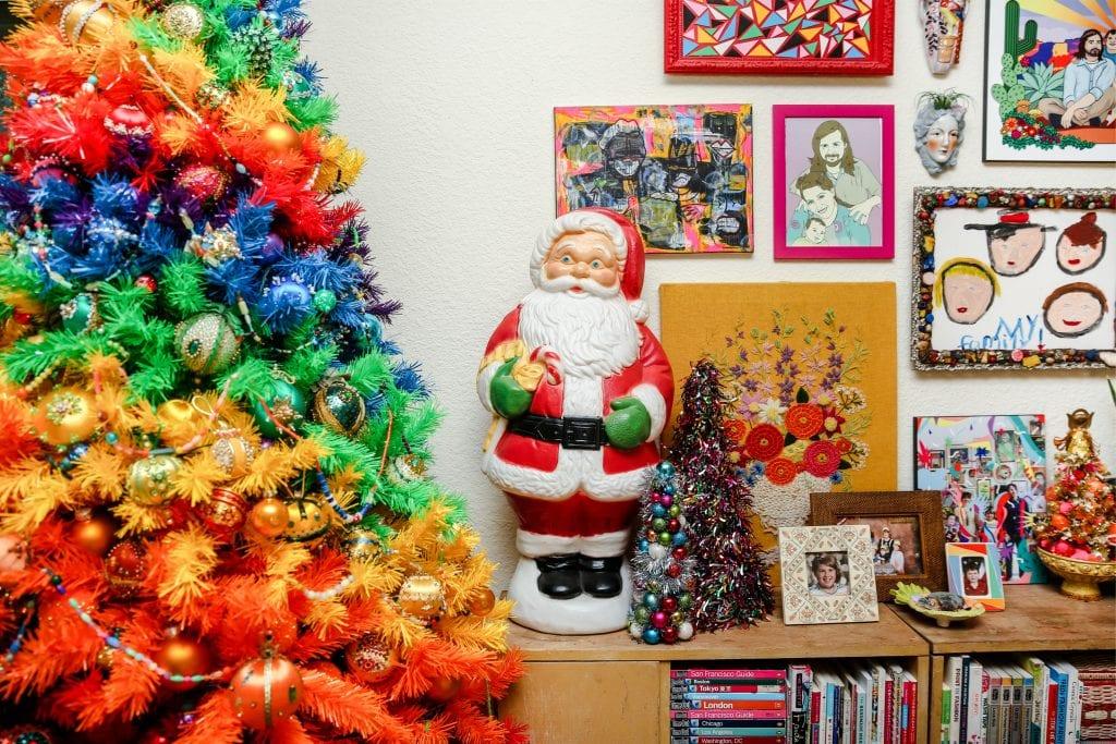 Santa blow mold next to a rainbow tree .