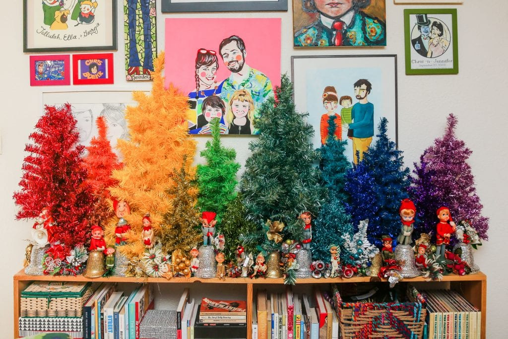 A collection of mini Christmas trees in rainbow order.