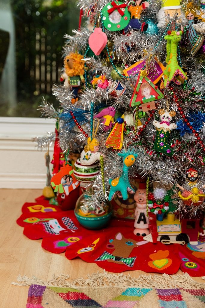 Flocked Christmas tree with handmade felt appliqué tree skirt and vintage toys.